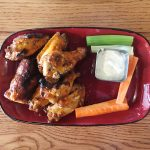 Palette 22 Grilled Cholula Butter Wings grill marks on a red plate with celery carrots and blue cheese dressing wood table
