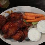 The Ugly Mug DC Mumbo Sauce Chicken Wings on a white plate with blue cheese carrots and celery and a beer